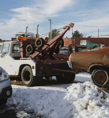 Tow truck picking up junk car