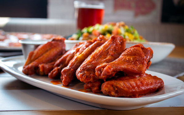 Chicken Wings with salad and beer in the background