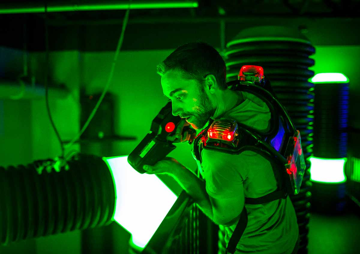 Man holding lasertag gun in green night vision light