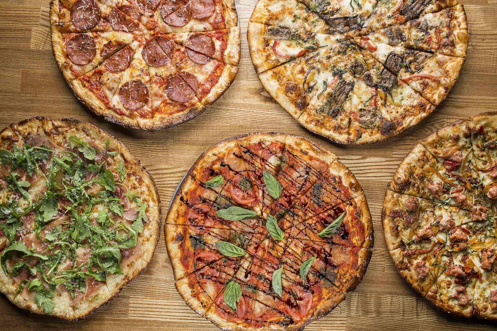 5 craft pizzas on wooden board