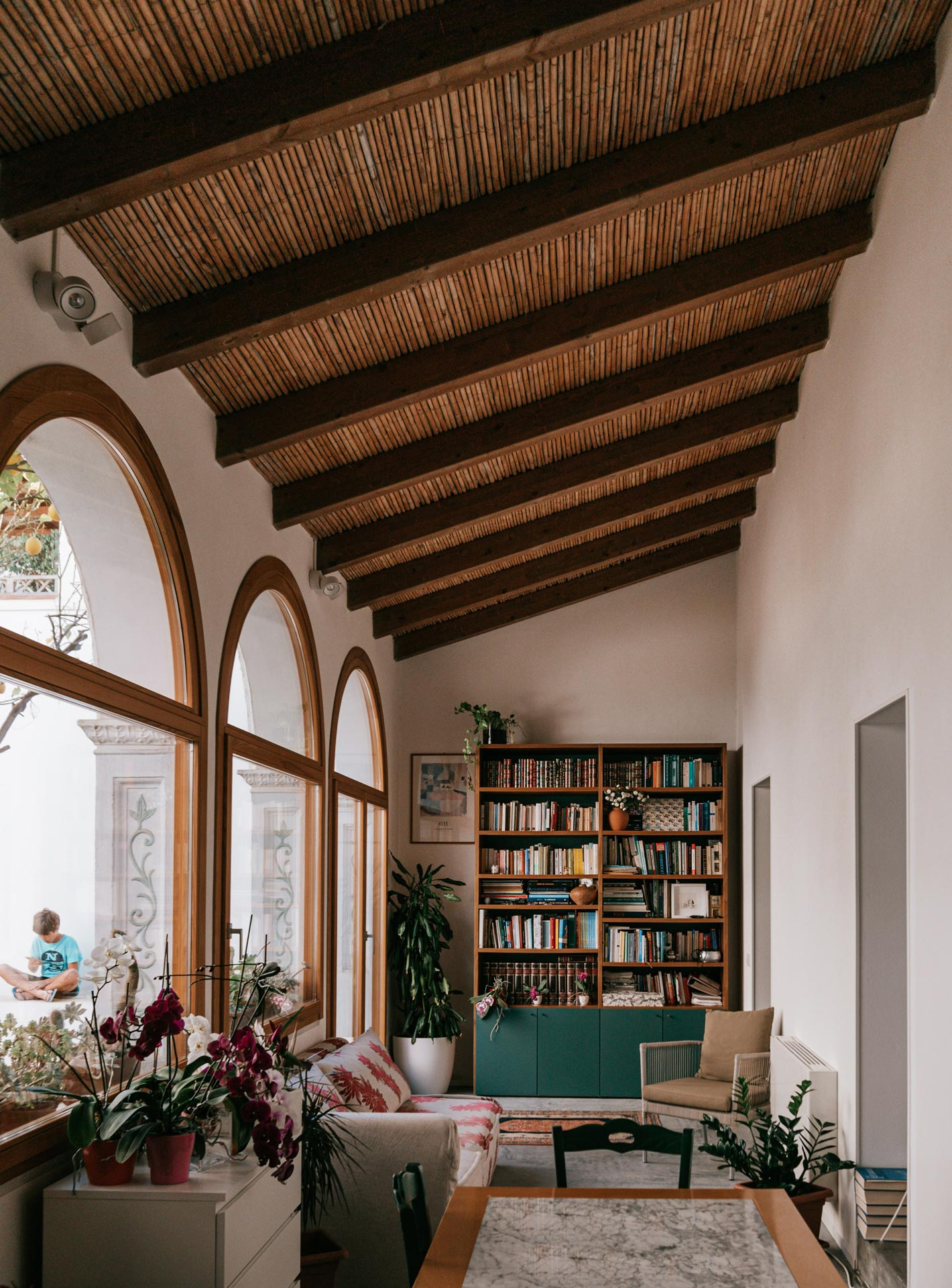 A living room with a slanted wooden ceiling with wooden beams, three arched windows, furniture, and a wooden bookcase with green cabinet drawers at the bottom.