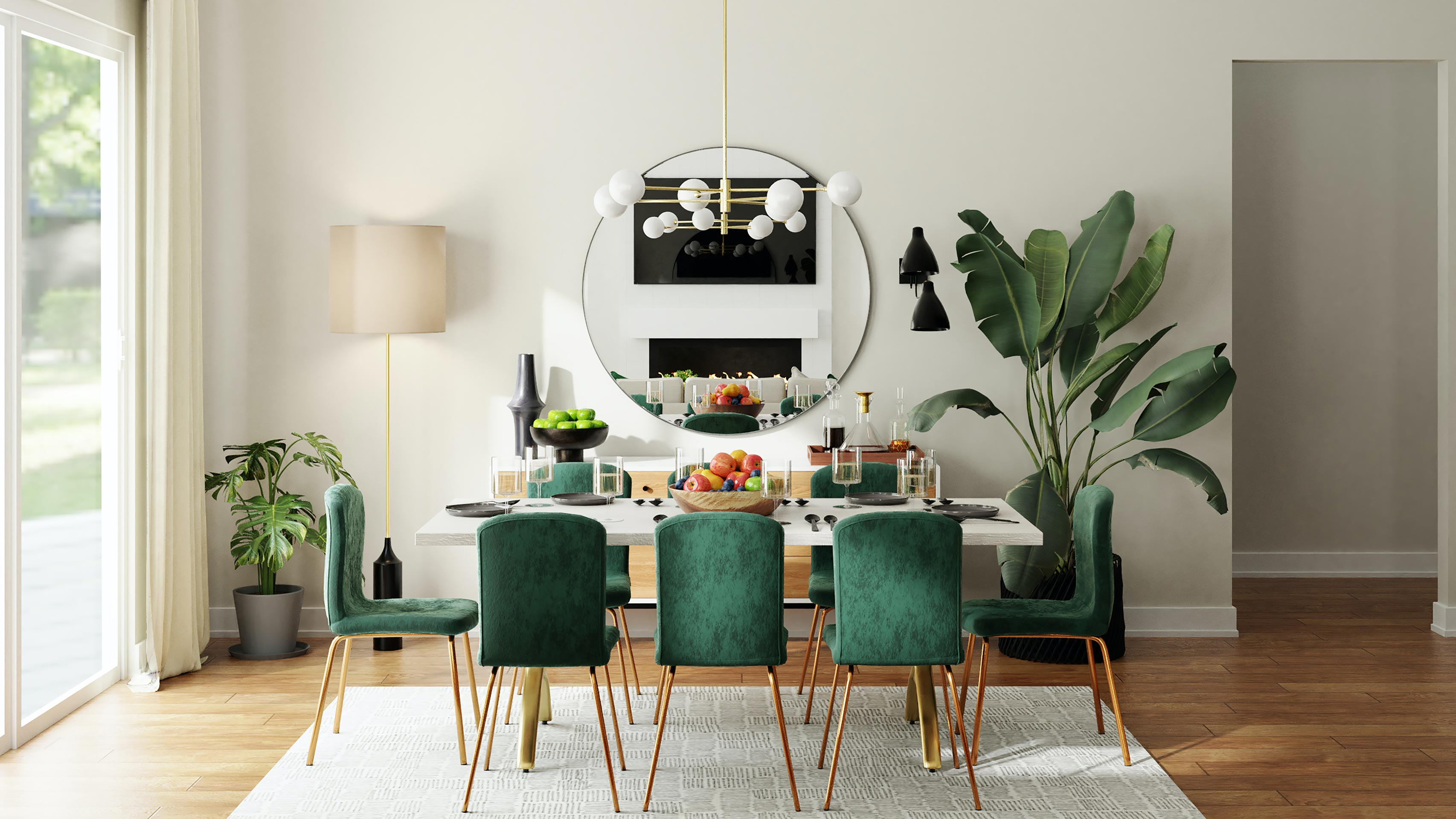 A dining room with a white dining table, emerald green velvet chairs, a large round mirror, a mid-century-modern light fixture and large plants.