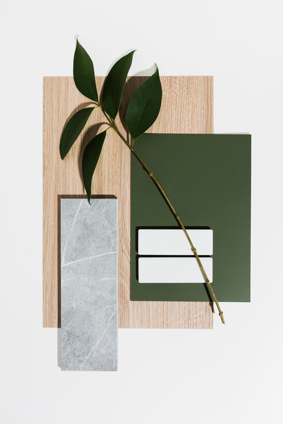 A flatlay consisting of wood, concrete tile, an olive green swatch and a plant branch.