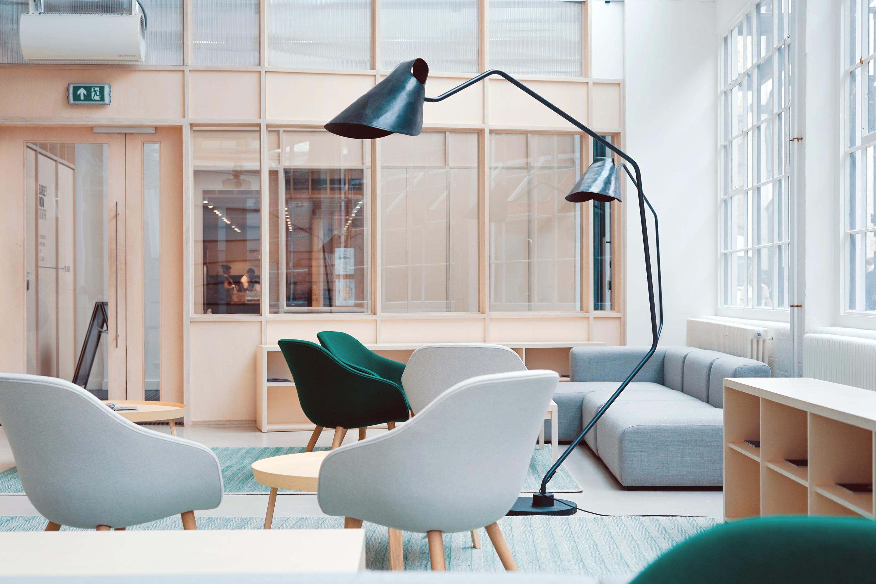 An office common area with a grey sofa, grey chairs, green chairs and a black lamp.