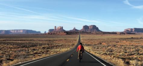 Biker on open desert road.