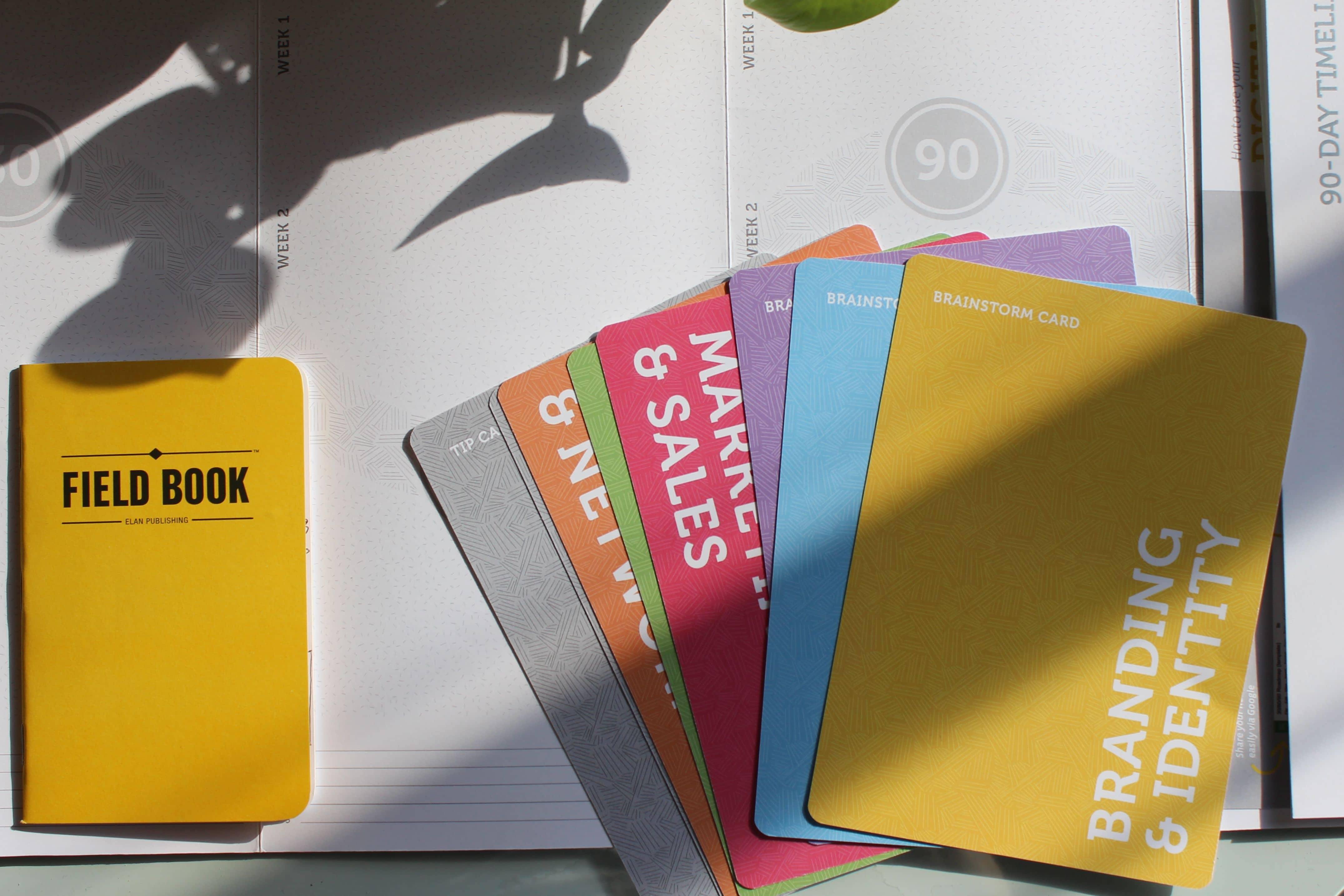 Product shot of Co.Starters materials including the field book and brainstorming cards.