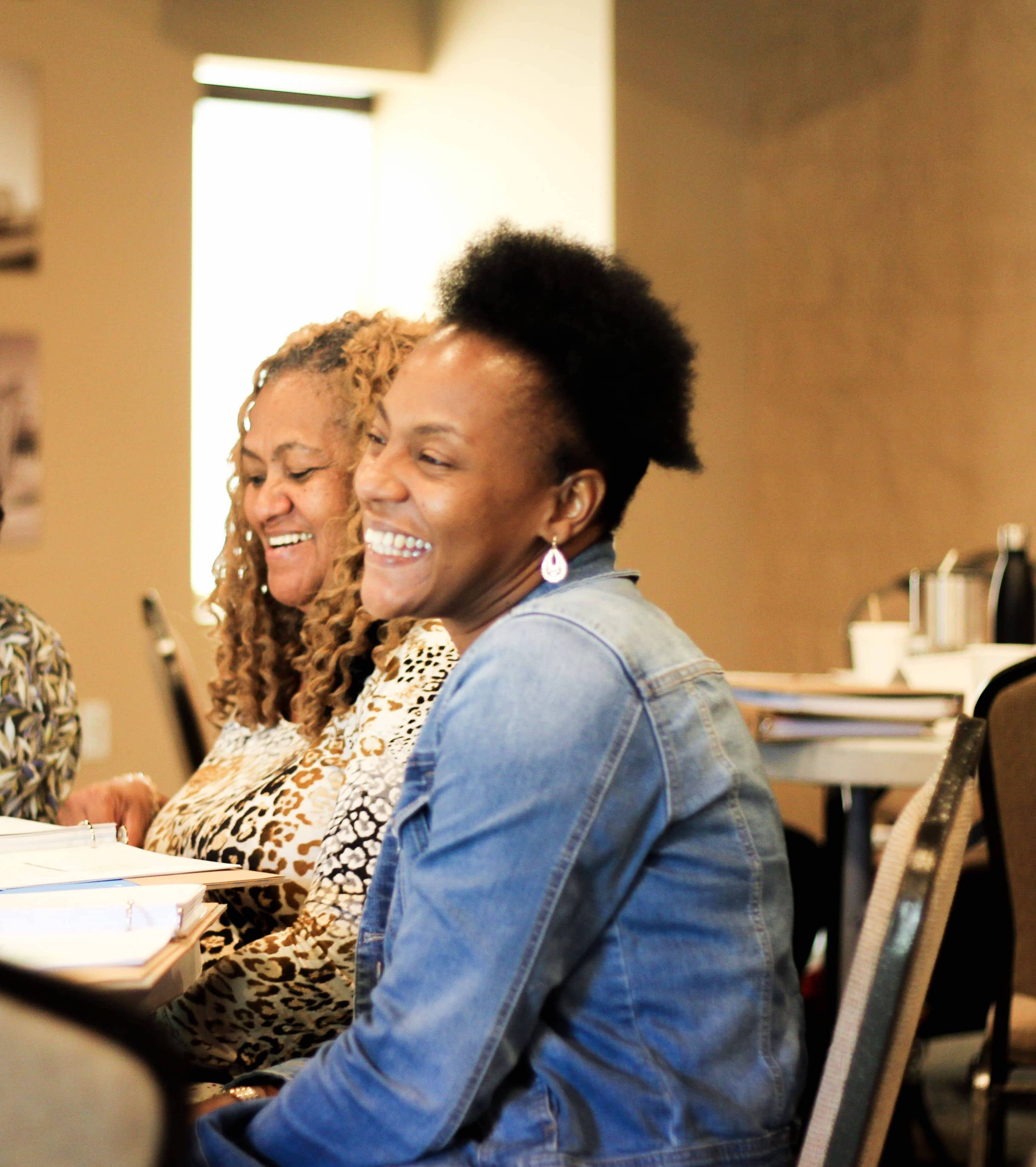 Two young black women smile as they listen to a presentation.