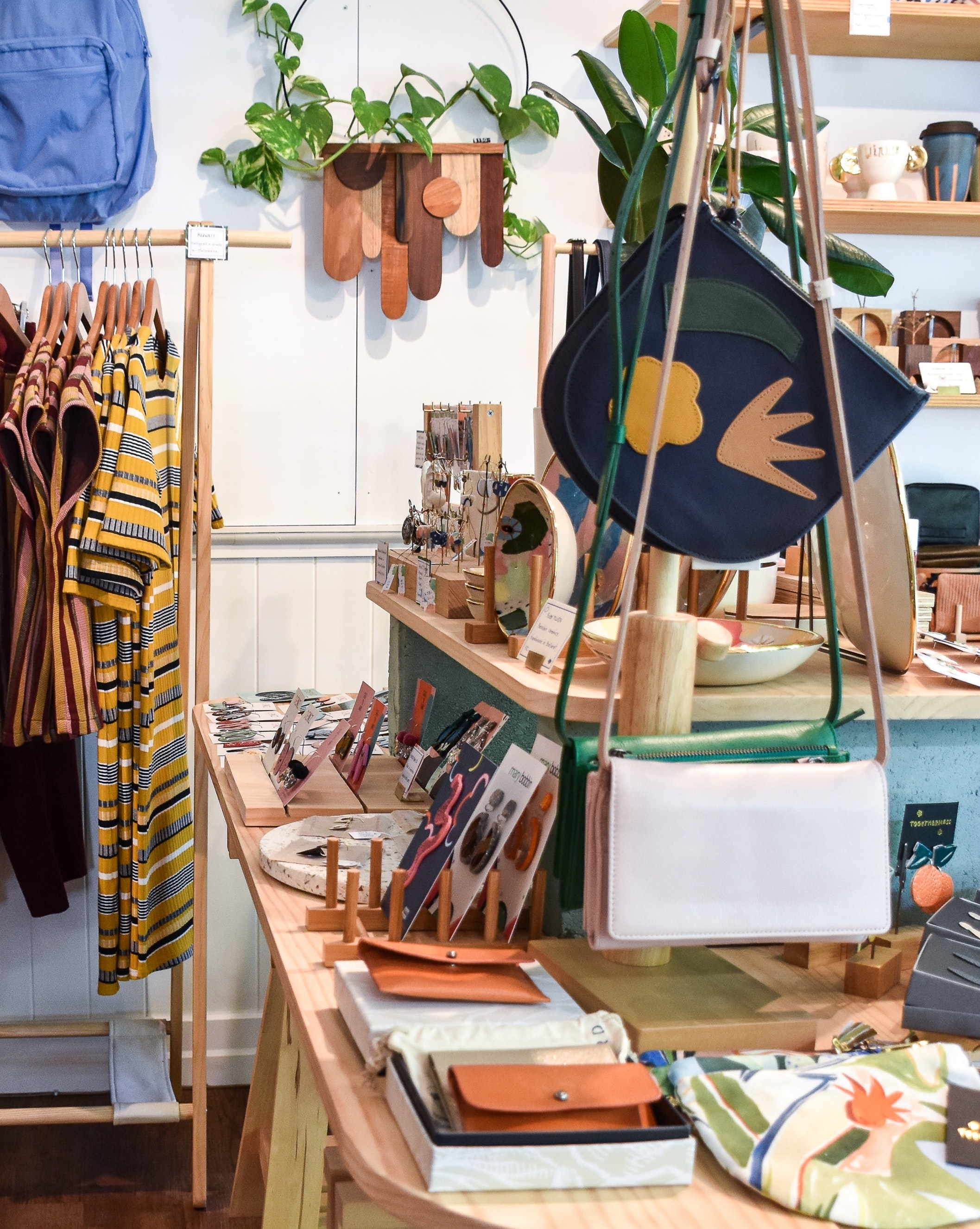 A photo of the interior of Square One Goods in Birmingham, AL. Lots of items are displayed like clothing, bags, clutches, and more.