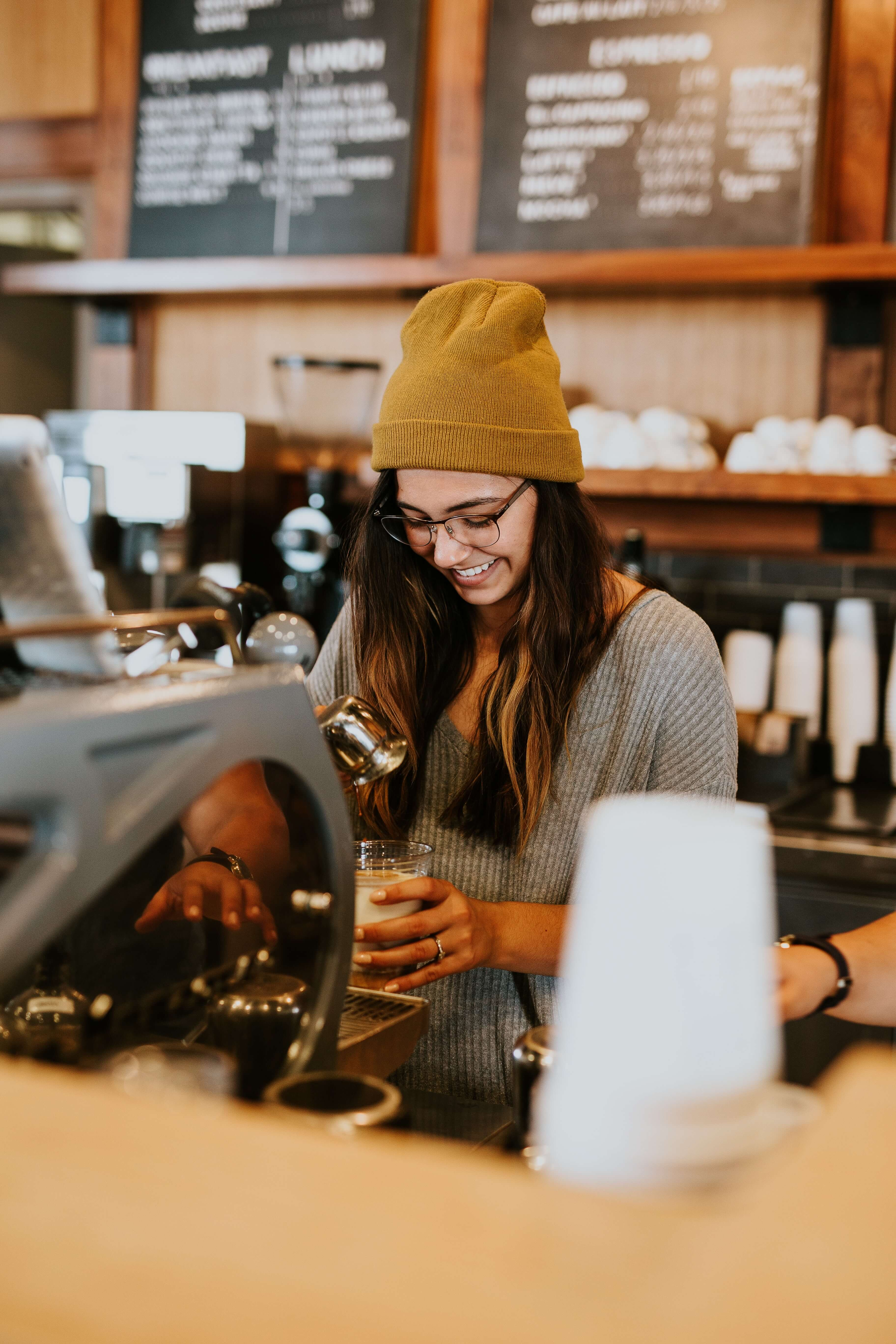 A young barista brews a cup of coffee.