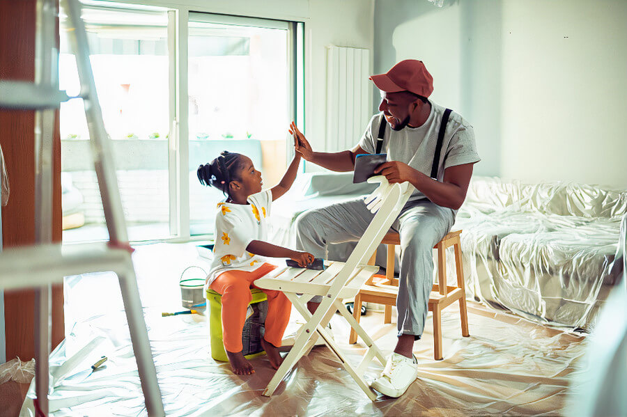 Man with daughter renovating a house