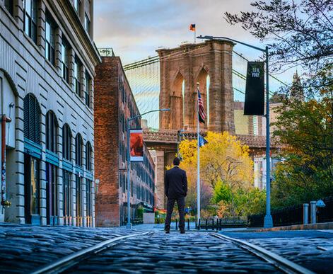 Man standing in front of Brooklyn Bridge