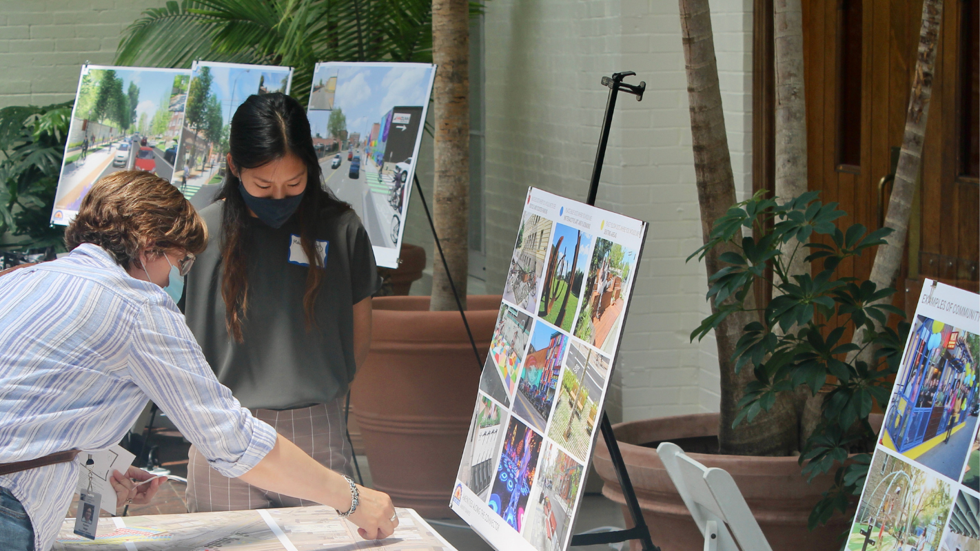 Two people look over plans at a table during community open house with boards on tripods showing example improvements