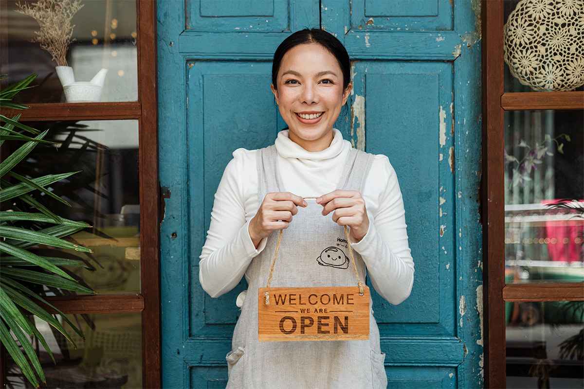 """A picture of a business owner holding a """"open for business"""" sign"""