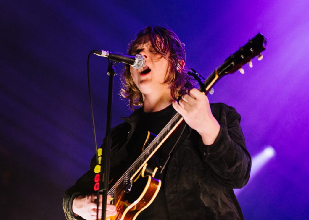 lewis capaldi performing on stage singing and playing guitar against a purple lit background