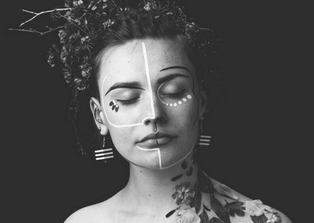 zoe bestel with flowers on her hair and face shot in black and white looking down