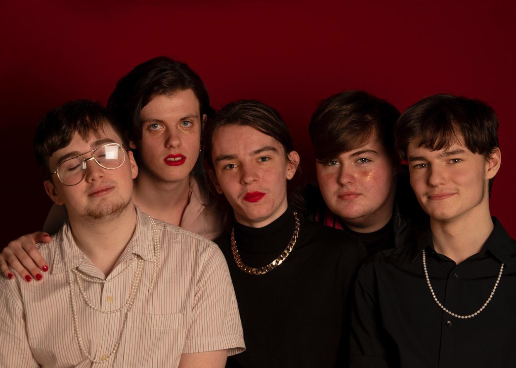 members of the band velvet standing closely together against red background