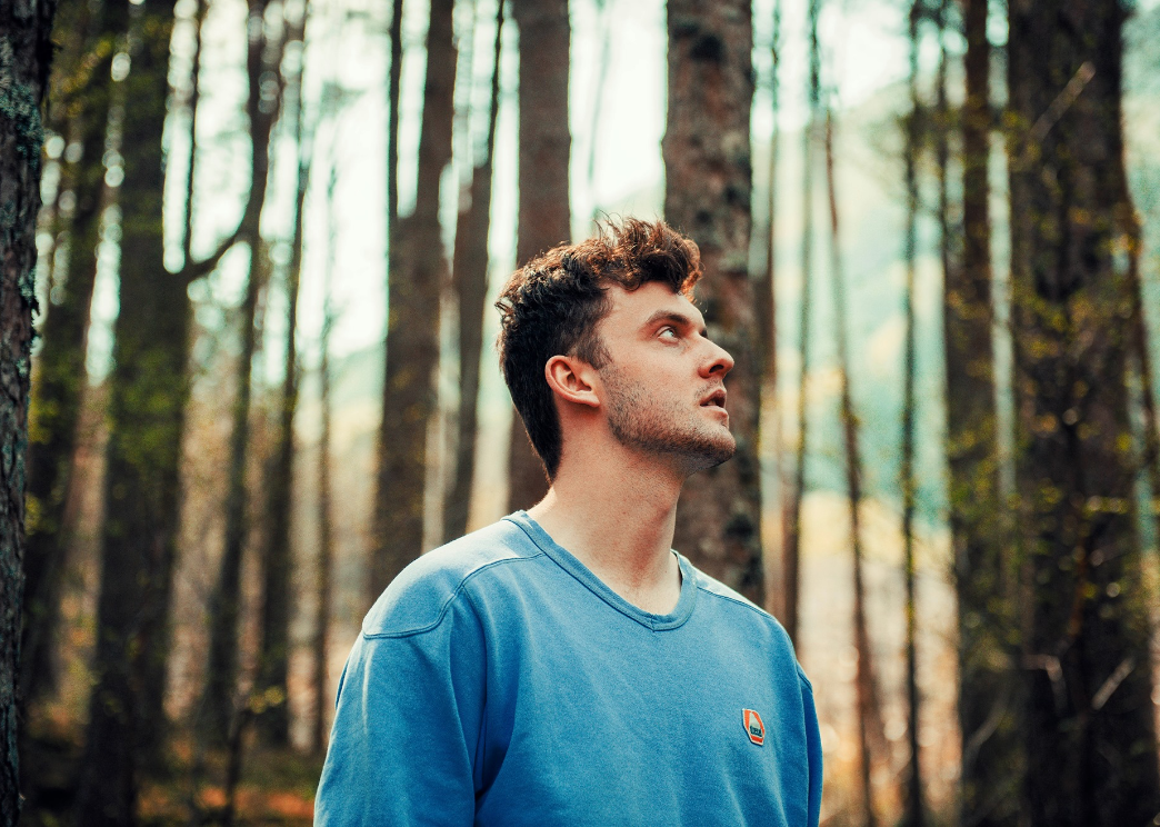 keir gibson standing in forest looking to the sky with tall trees around him