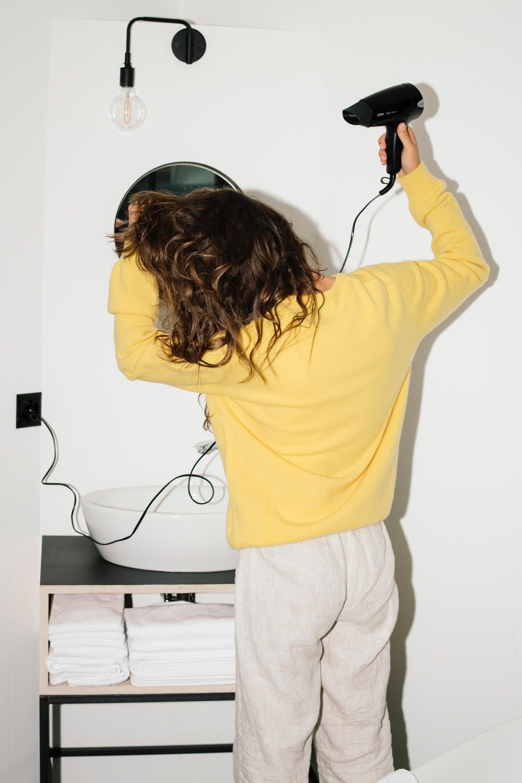 Frau föhnt sich die Haare