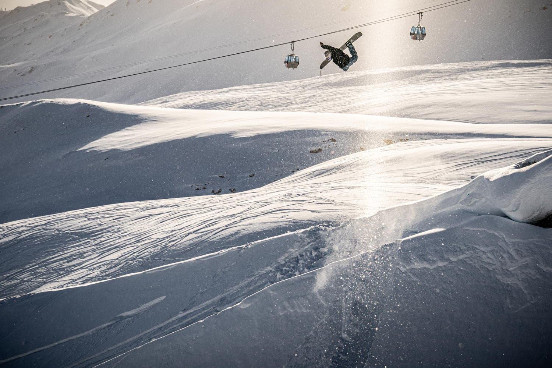 Snowboarder jumped über Kicker vor dem Skilift