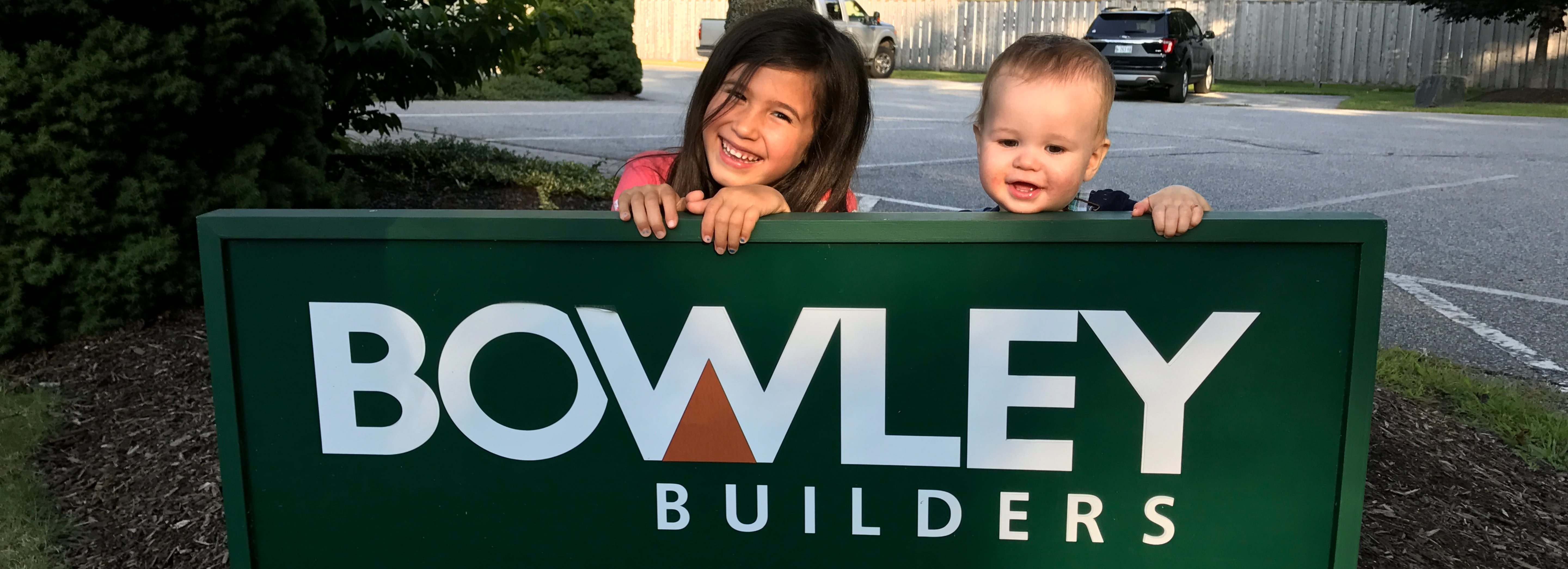 Two children hanging on a Bowley Builders sign