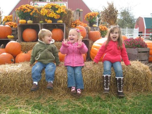 Picture of three kids sitting on a haystack laughing.