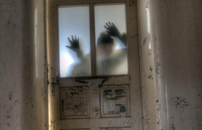 Haunted house with scary figures breaching a door.