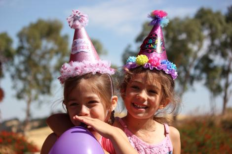 Two girls at a kid's birthday party.