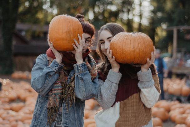 Two girls holding pumpkins.