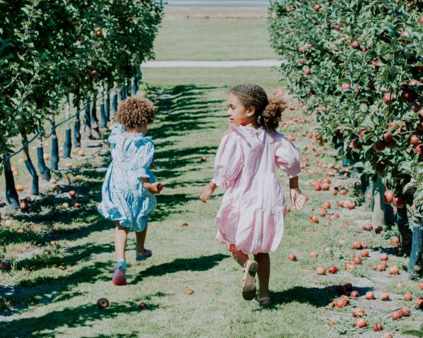 Girls running in an apple orchard.