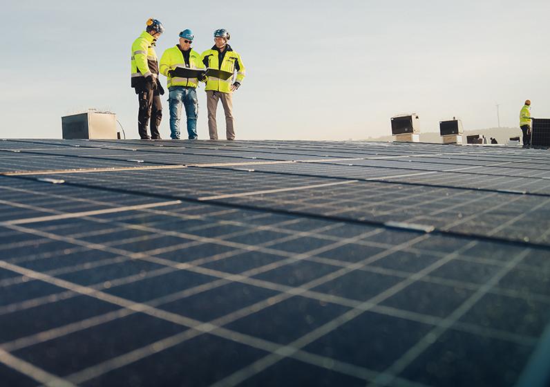 En tak med solceller och byggarbetare