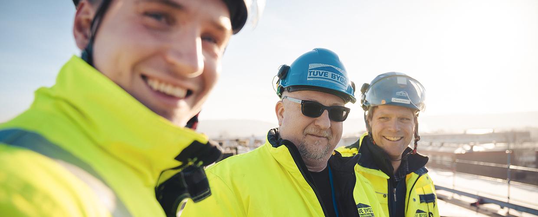 Tre byggarbetare som ler mot kameran