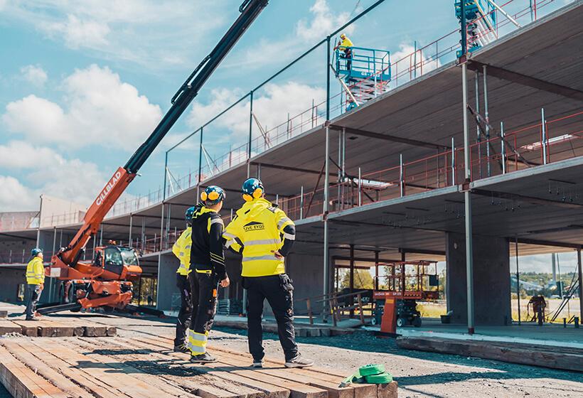 Byggarbetare som kollar upp mot en byggnad