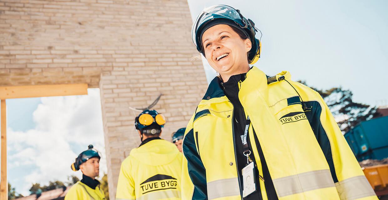 En tjej som ler på byggarbetsplats