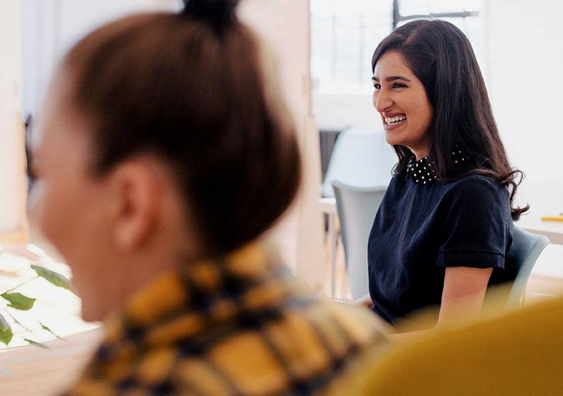 Två tjejer som ler på ett kontor
