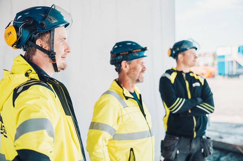 Tre byggarbetare som kollar på något