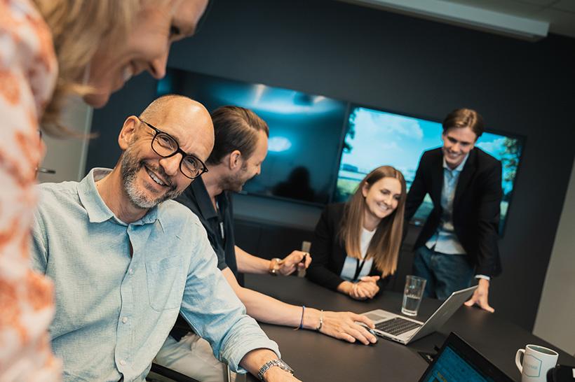 Människor som ler i ett möte på ett kontor