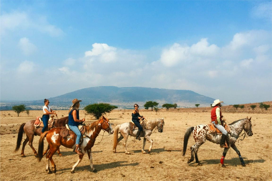 horse riders riding on the open field in mexico at rancho las cascadas