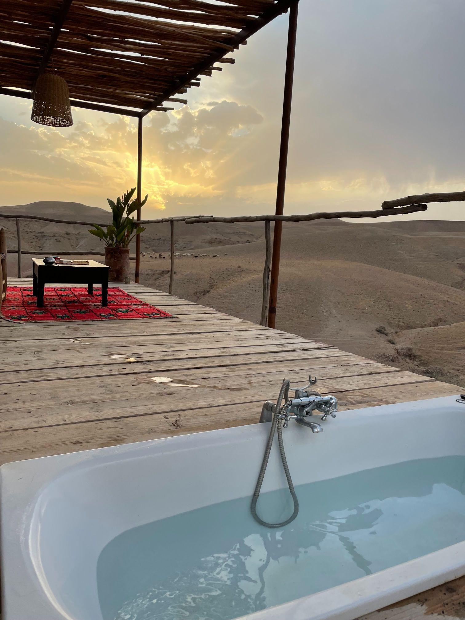bathtub on porch in agafay desert morocco sunrise
