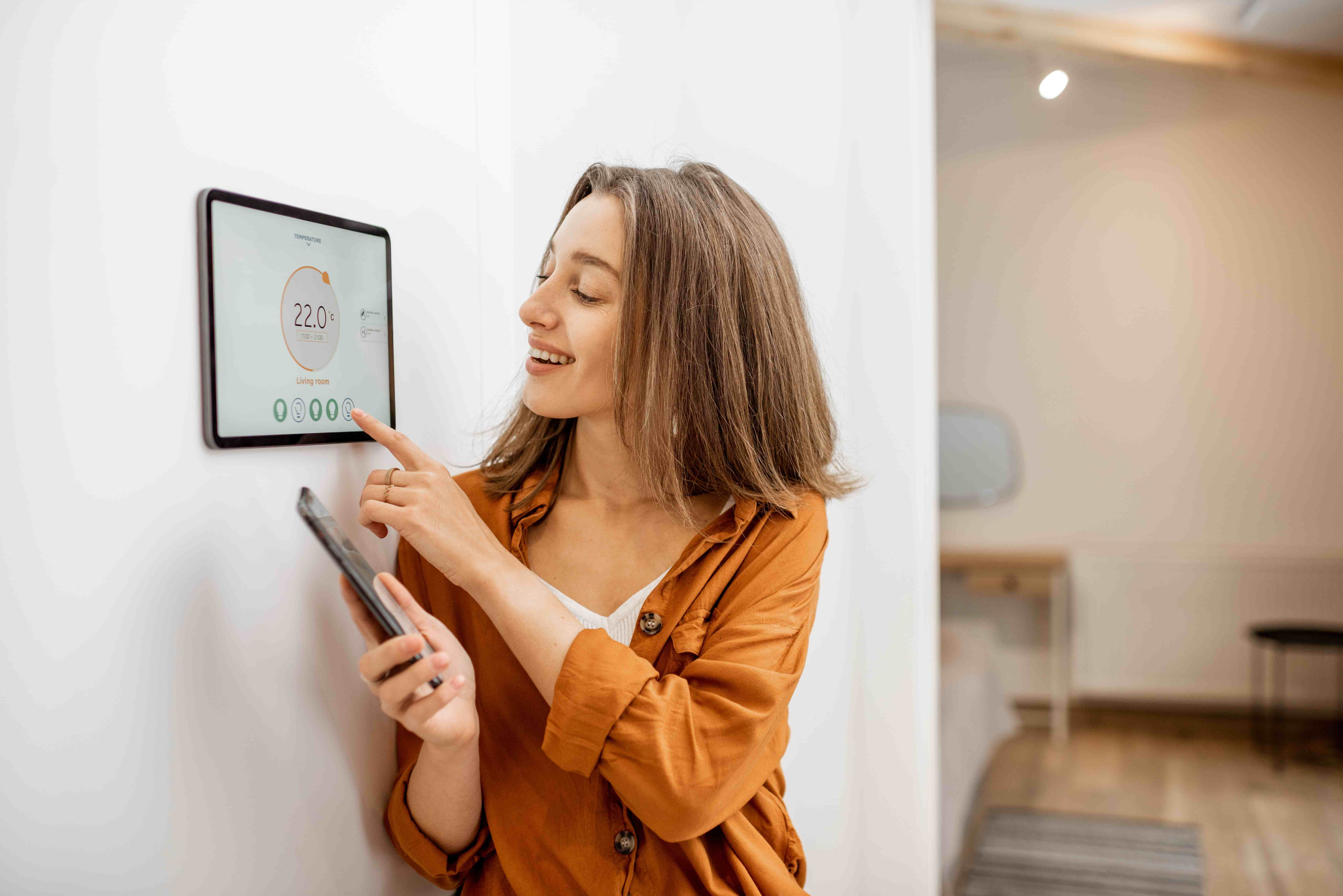 Woman controlling temperature with Smart Thermostats