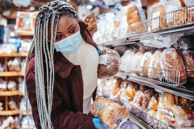 Vrouw met mondkapje die staat voor het broodschap en een keuze probeert te maken.