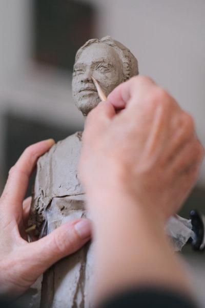 Eine Figur aus Ton wird mit Händen modelliert