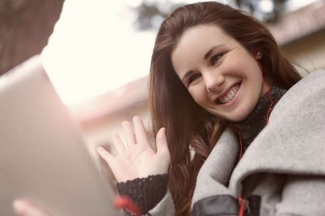 woman-in-black-and-gray-coat-wearing-red-earphones-3783110