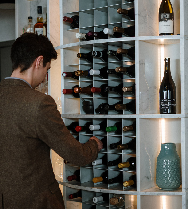 Man selecting a wine from a wall of wines