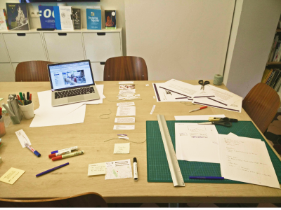 A desk with cut pieces that were used to create a paper prototype of Stepstone's job listing