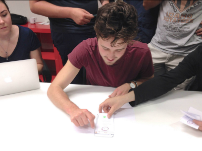 One person is testing a paper prototype while others are observing him