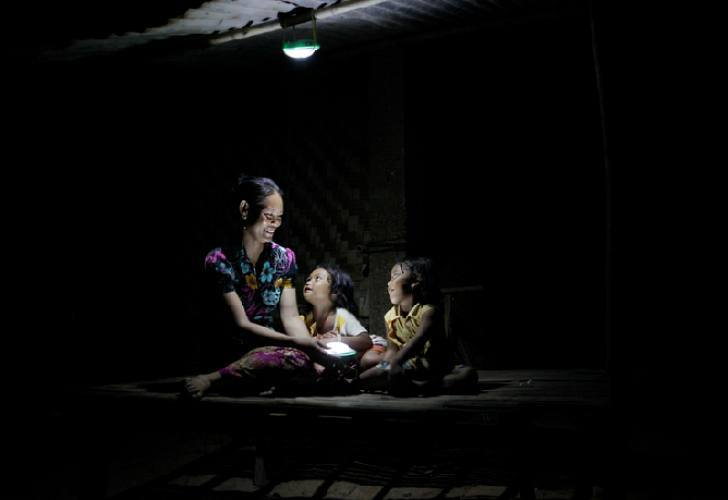 A mother with her two children under the light of the Moonlight lamp