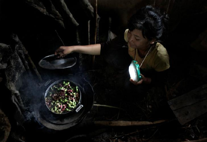 A woman cooking under the light of a Moonlight lamp that is hanging from her neck