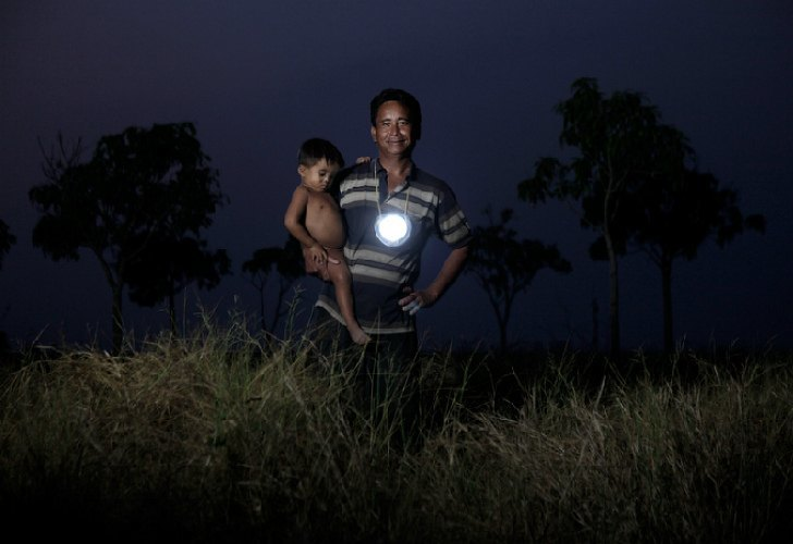 A man with a boy out in the dark with a Moonlight lamp hanging from his neck