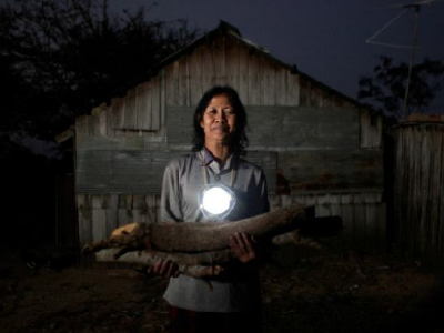 Cambodian woman posing in the dark with a Moonlight lamp hanging  from her neck
