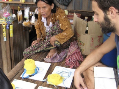 Loucas Papantoniou showing paper prototypes of the Moonlight lamp to a Cambodian woman